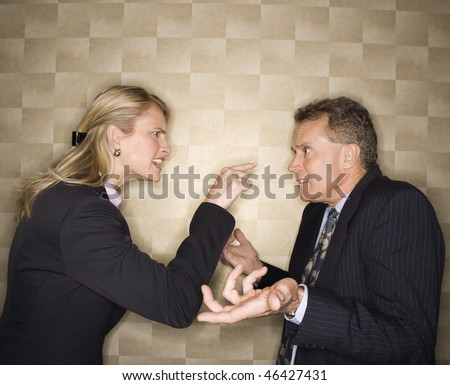 Caucasian mid-adult businesswoman yelling and pointing at middle-aged businessman, who shrugs at her. Horizontal format. - stock photo