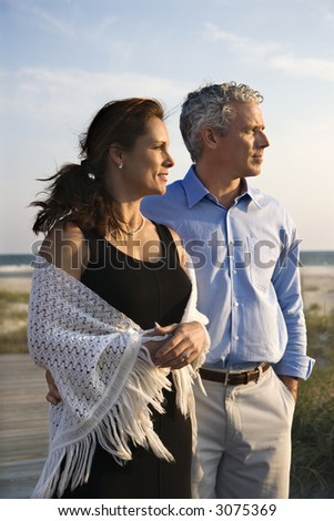 Caucasian mid-adult coulpe looking off to side at beach. - stock photo