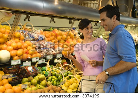 Caucasian mid-adult couple grocery shopping for fruit looking at each other smiling.
