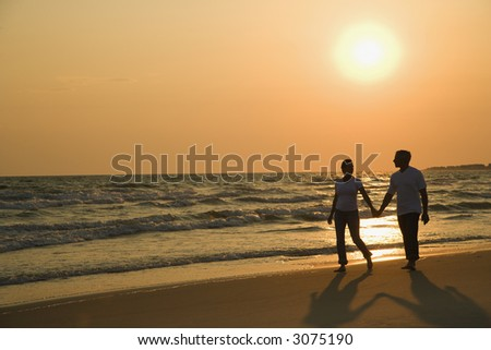 Caucasian mid-adult couple holding hands and walking down beach at sunset. - stock photo