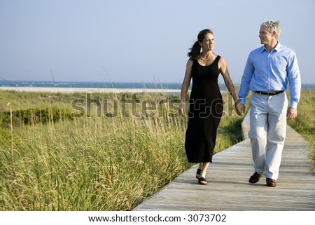 Caucasian mid-adult couple holding hands and walking on walkway. - stock photo