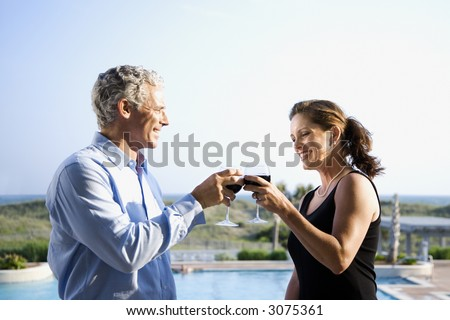 Caucasian mid-adult couple making toast with wine glasses. - stock photo