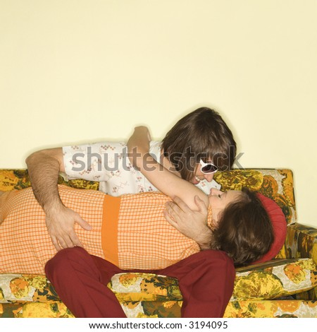 Caucasian mid-adult couple smiling and embracing on colorful retro sofa. - stock photo