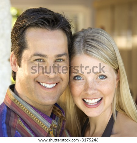 Caucasian mid adult couple smiling at viewer.