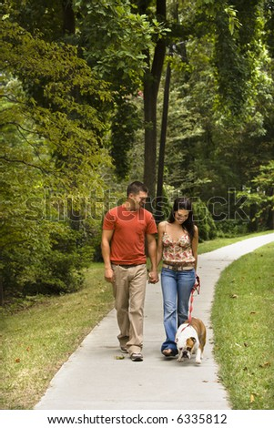 Caucasian mid adult couple walking English Bulldog in park. - stock photo
