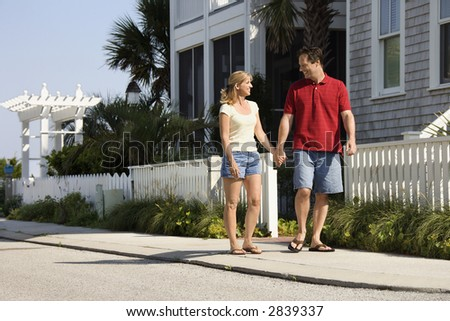 Caucasian mid-adult couple walking on suburban sidewalk holding hands. - stock photo