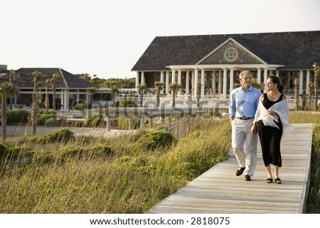Caucasian mid-adult couple walking on walkway near beach home. - stock photo