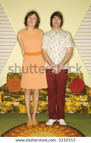 Caucasian mid-adult couple wearing retro clothes standing in room decorated with vintage furniture. - stock photo