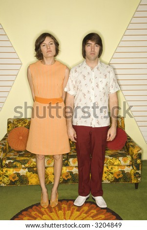 Caucasian mid-adult couple wearing retro clothes standing stiffly in room decorated with vintage furniture. - stock photo