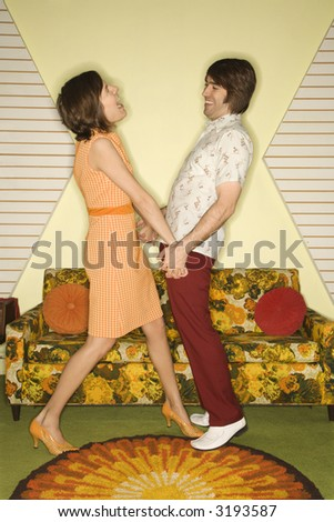 Caucasian mid-adult couple wearing vintage clothing looking at each other laughing and holding hands. - stock photo