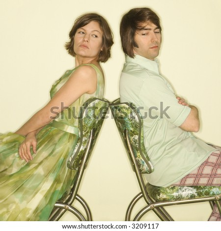 Caucasian mid-adult couple wearing vintage clothing sitting back to back in green vinyl chairs with arms crossed looking angry. - stock photo