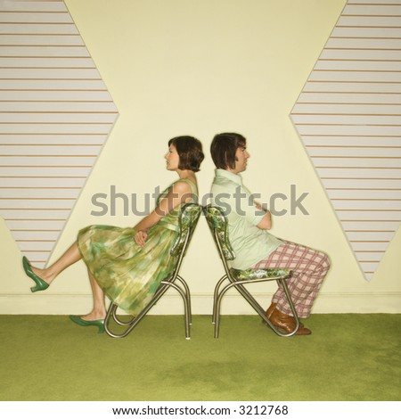 Caucasian mid-adult couple wearing vintage clothing sitting back to back in green vinyl chairs with arms crossed. - stock photo