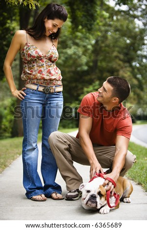 Caucasian mid adult couple with English Bulldog on sidewalk. - stock photo