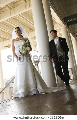 Caucasian mid-adult fbride and groom standing on porch.