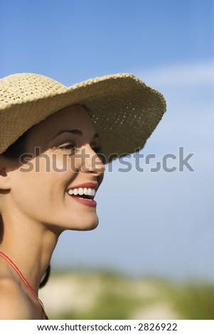 Caucasian mid-adult female in swimsuit and straw hat.
