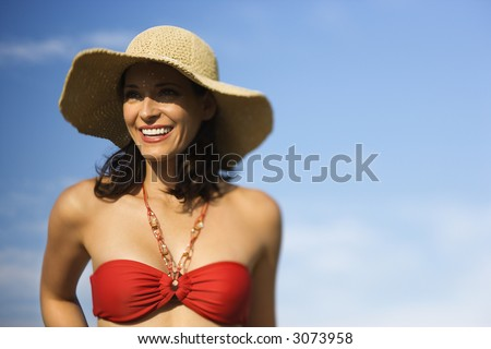 Caucasian mid-adult female in swimsuit and straw hat. - stock photo