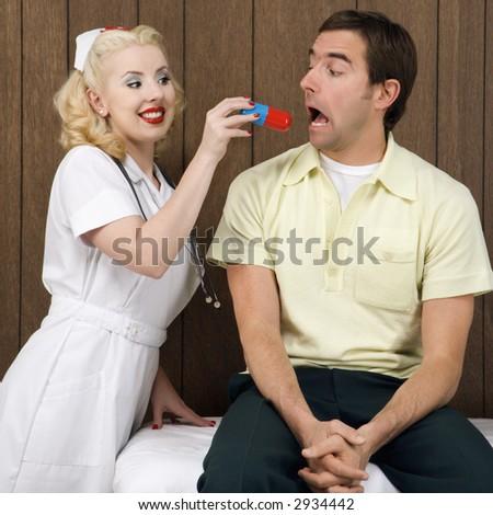 Caucasian mid-adult female nurse  giving mid-adult man giant pill. - stock photo