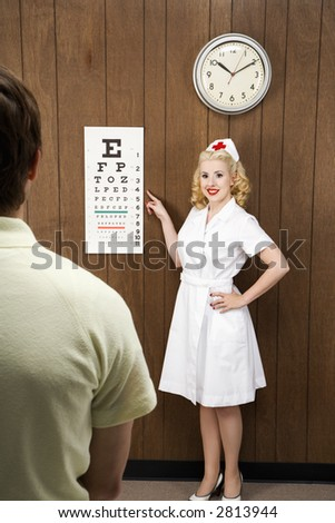 Caucasian mid-adult female nurse  pointing out eye chart to mid-adult male patient.
