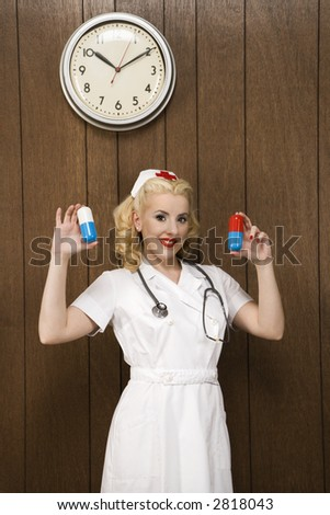 Caucasian mid-adult female nurse standing by wood paneling holding oversized pills and smiling at viewer.