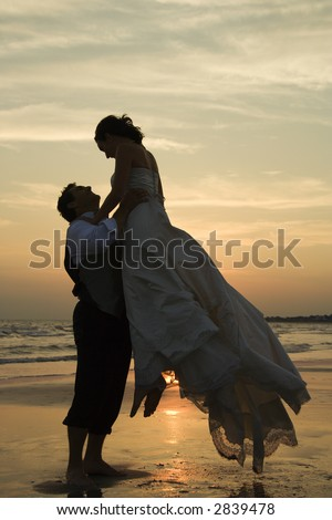Caucasian mid-adult groom lifting up bride on beach at sunset.
