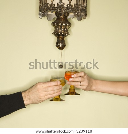 Caucasian mid-adult male and female hands toasting glasses.