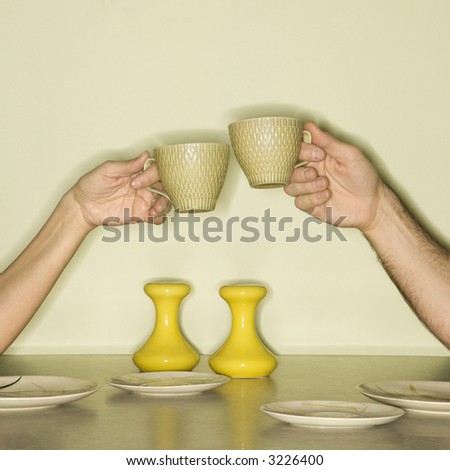 Caucasian mid-adult male and female hands toasting with coffee cups across retro kitchen table setting. - stock photo