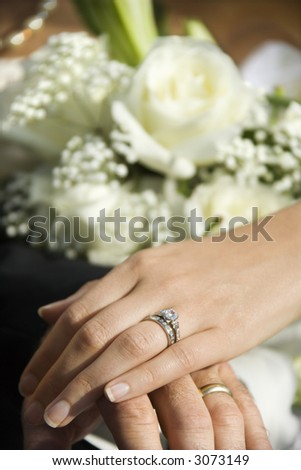 Caucasian mid-adult male and female hands with wedding rings. - stock photo