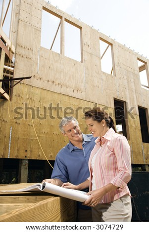 Caucasian mid-adult male and female looking at blueprints in construction phase of house. - stock photo
