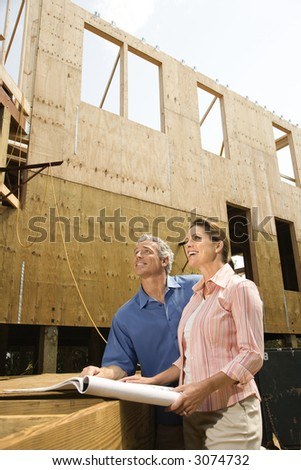 Caucasian mid-adult male and female with blueprints observing building construction site. - stock photo