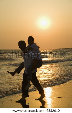 Caucasian mid-adult male carrying female piggyback on beach at sunset.