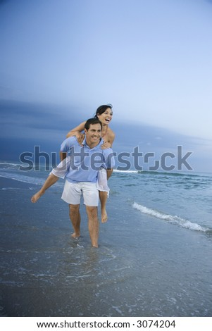 Caucasian mid-adult male carrying female piggyback style on beach.
