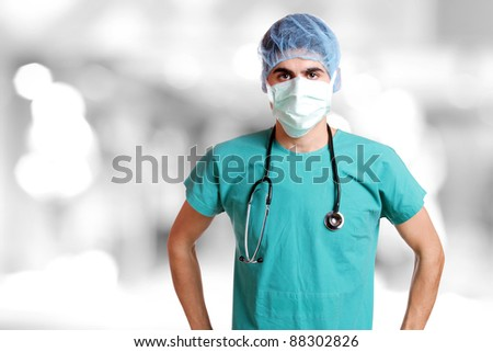 Caucasian mid adult male doctor wearing a mask over bokeh background - stock photo