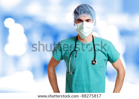 Caucasian mid adult male doctor wearing a mask over bokeh blue background - stock photo