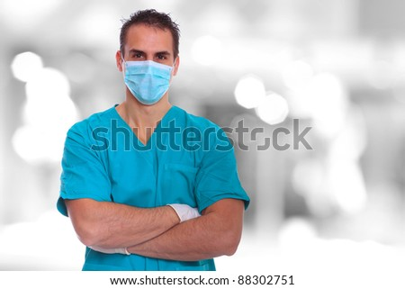 Caucasian mid adult male doctor wearing a mask over bokeh blue background