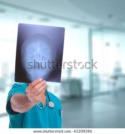 Caucasian mid adult male doctor with xray posing over light medical environment background - stock photo