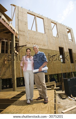 Caucasian mid-adult male holding blue prints with arm around mid-adult female in building construction site. - stock photo
