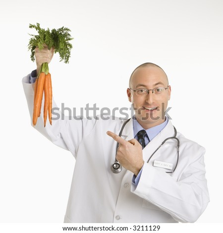 Caucasian mid adult male physician holding and pointing to bunch of carrots. - stock photo