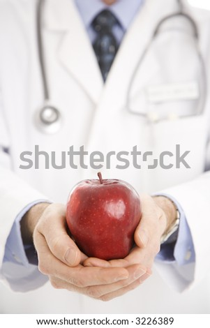 Caucasian mid adult male physician holding apple. - stock photo