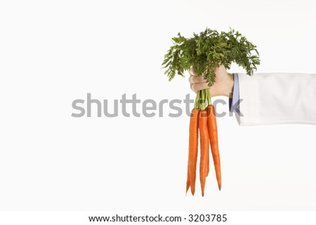 Caucasian mid adult male physician holding bunch of carrots. - stock photo