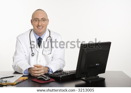 Caucasian mid adult male physician sitting at desk smiling with laptop computer. - stock photo