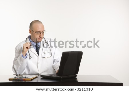 Caucasian mid adult male physician sitting at desk with laptop computer. - stock photo