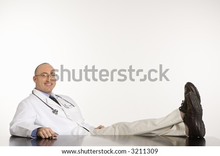 Caucasian mid adult male physician sitting with feet on desk smiling. - stock photo