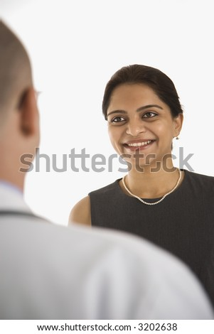 Caucasian mid adult male physician talking with Indian woman patient. - stock photo