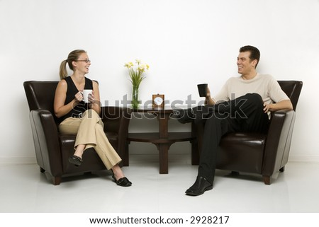 Caucasian mid-adult man and woman sitting in armchairs drinking coffee. - stock photo