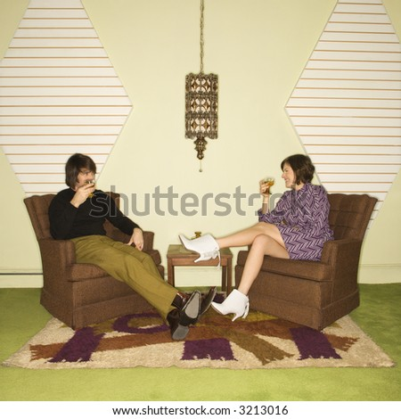 Caucasian mid-adult man and woman wearing vintage clothing seated in brown retro chairs smiling and drinking. - stock photo
