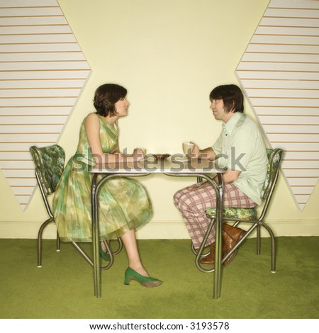 Caucasian mid-adult man and woman wearing vintage clothing sitting at 50's retro dinette set facing each other. - stock photo