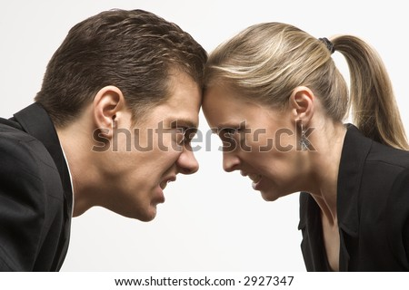 Caucasian mid-adult man and woman with foreheads together staring at each other with hostile expressions. - stock photo