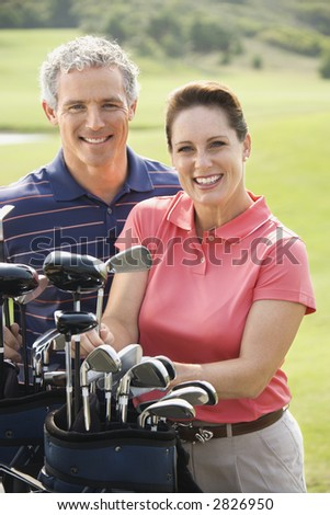 Caucasian mid-adult man and woman with golf clubs smiling and looking at viewer. - stock photo