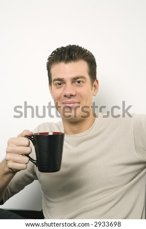 Caucasian mid-adult man holding coffee cup and looking at viewer.