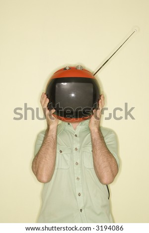 Caucasian mid-adult man holding round red retro television in place of head. - stock photo